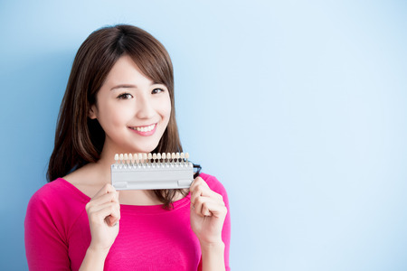 beauty woman hold teeth whitening tool isolated on blue background Stock Photo
