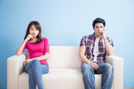 young couple feel bad and look somewhere sit on sofa at home Фото со стока
