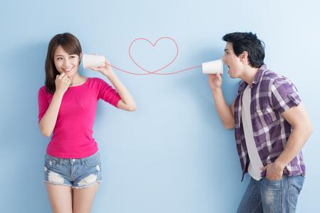 jeune couple avec boîte téléphone isolé sur fond bleu