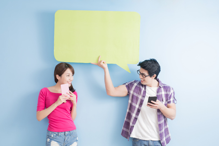 young couple take phone and speech bubble isolated on blue background Banco de Imagens