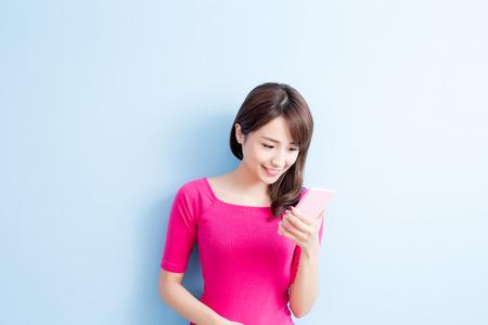 青の背景に分離された美しさ女性使用携帯電話