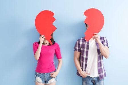 joven pareja tener corazón roto aislados sobre fondo azul