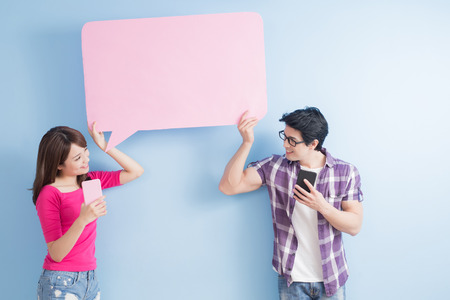 happy couple: young couple take phone and speech bubble isolated on blue background Stock Photo