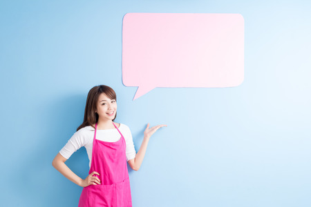 asian chef: beauty housewife take speech bubble billboard and smile isolated on blue background