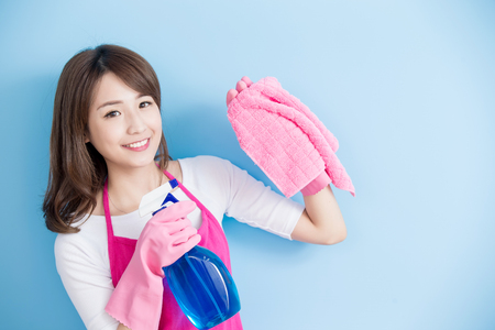 asian lady: beauty housewife take rag and detergent isolated on blue background, asian Stock Photo