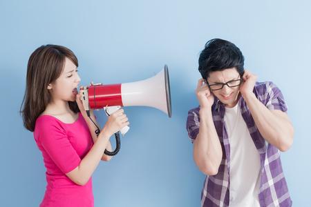 mujer toma el grito de micrófono al hombre enojado aislado sobre fondo azul
