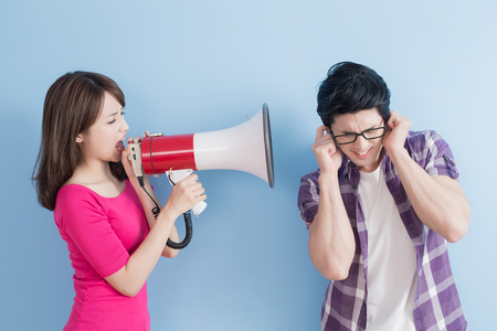 woman take the microphone shout to man angrily isolated on blue background Stock Photo