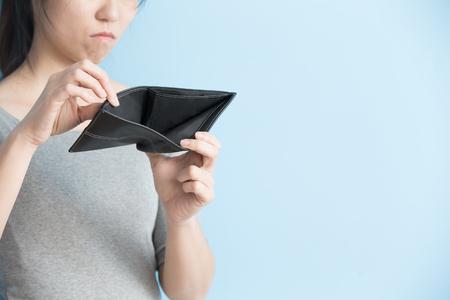 mujer con dinero en su billetera pantalones