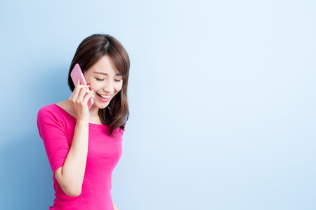 beauty woman talk on phone isolated on blue background Reklamní fotografie