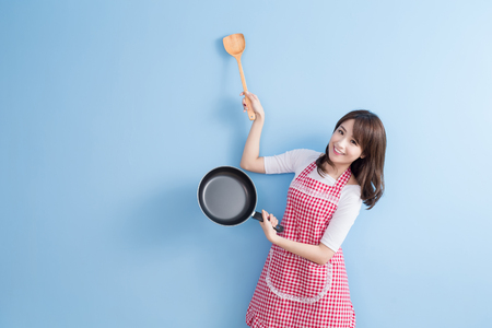 esposas: la belleza del ama de casa toma wok y arroz cuchara aislados sobre fondo azul Foto de archivo