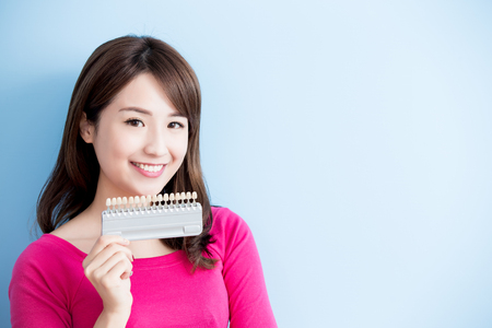 beauty woman hold teeth whitening tool isolated on blue background 版權商用圖片