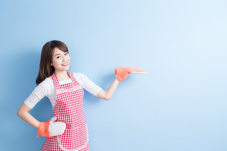 beauty housewife show something and wear gloves isolated on blue background