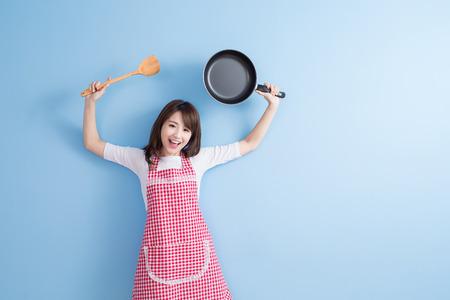 Schönheit Hausfrau nehmen Wok und Reis Löffel auf blauem Hintergrund isoliert Standard-Bild - 70046849