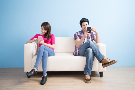 young couple play phone happily at home