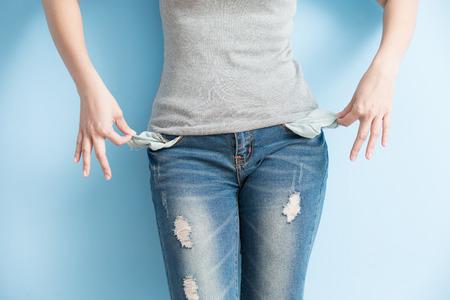 彼女を示す彼女の空のポケットを示す女性にはお金がないです。 写真素材