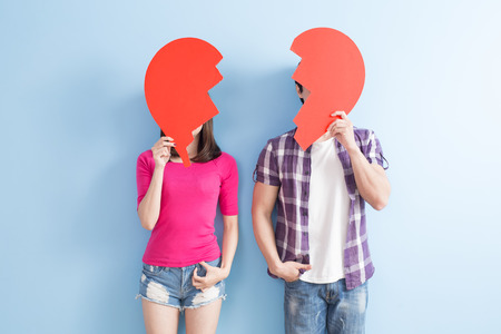 young couple take broken heart isolated on blue background