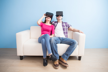 young couple watch vr game and smile happily isolated on blue background