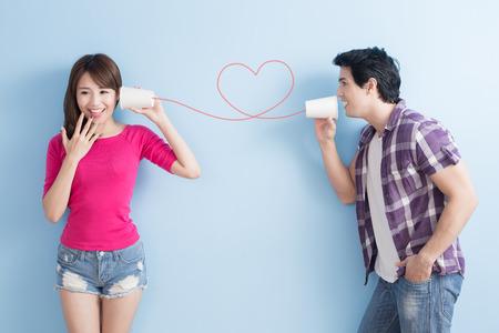 escuchar: joven pareja con el teléfono puede aislado en el fondo azul
