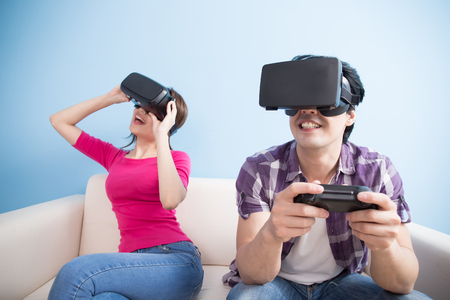 couple on couch: young couple play vr game isolated on blue background