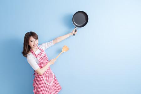 La belleza del ama de casa toma wok y arroz cuchara aislados sobre fondo azul Foto de archivo - 70047094