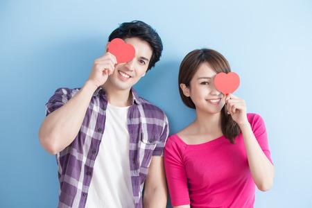 赤を抱いた魅力的な若い夫婦青い背景で隔離の目の上の心を愛します。 写真素材