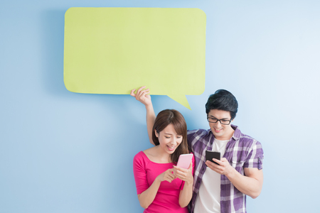 comunicarse: young couple take phone and speech bubble isolated on blue background Foto de archivo
