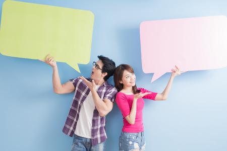 若いカップルが青の背景に分離した吹き出しを取る 写真素材