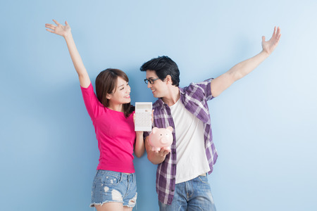 calculator chinese: young couple hold pink pig bank and calculator isolated on blue background