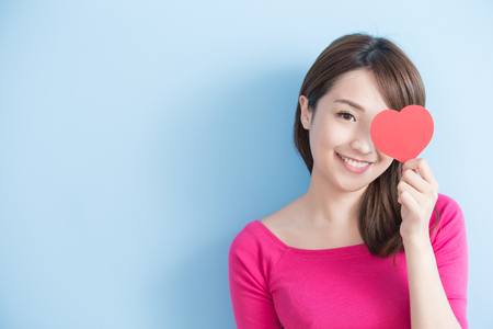 Attractive young woman holding red love hearts over eyes isolated on blue background