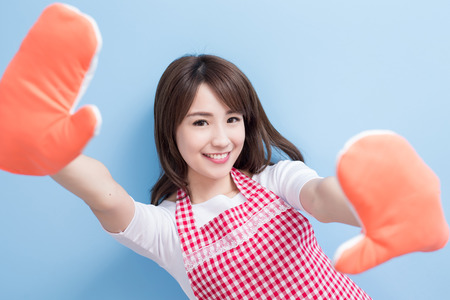 beauty housewife smile and wear gloves isolated on blue background
