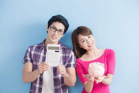 men and women: young couple hold pink pig bank and calculator isolated on blue background