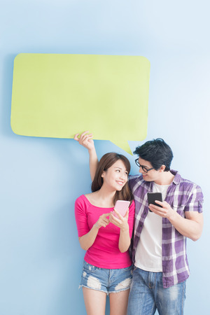 young couple take phone and speech bubble isolated on blue background Banque d'images