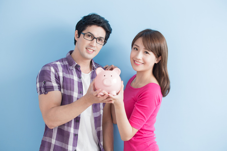 young couple hold pink pig bank and smile happily isolated on blue background Stock Photo