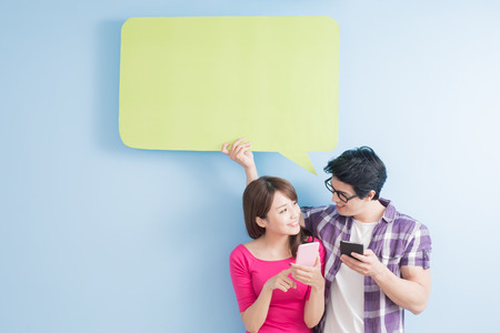 young couple take phone and speech bubble isolated on blue background Stok Fotoğraf