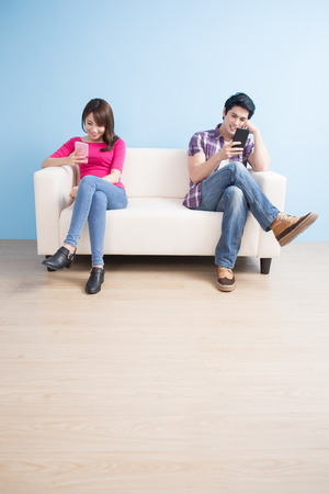 young couple look phone happily at home Stock Photo