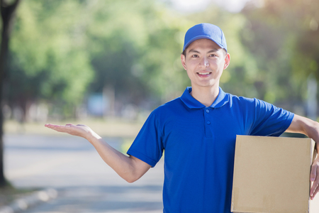 heavy: deliveryman hold  box and show something, asian