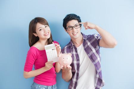 젊은 부부 핑크 돼지 은행 및 계산기 파란색 배경에 고립 개최
