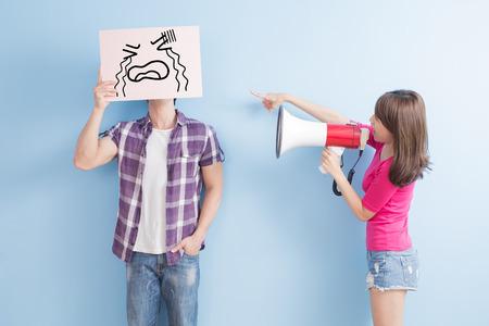 ruido: La mujer toma el grito micrófono al hombre enfadado aislado sobre fondo azul