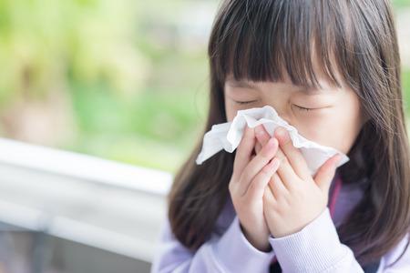 estornudo: niña se enfríe y sonarse la nariz, asiático Foto de archivo
