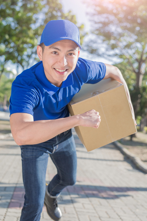 deliveryman hold box and smile to you, asian Stock Photo