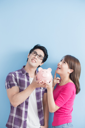 young couple hold pink pig bank and look somewhere isolated on blue background 版權商用圖片