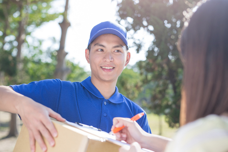 warehouseman: deliveryman stand and smile to customer, asian