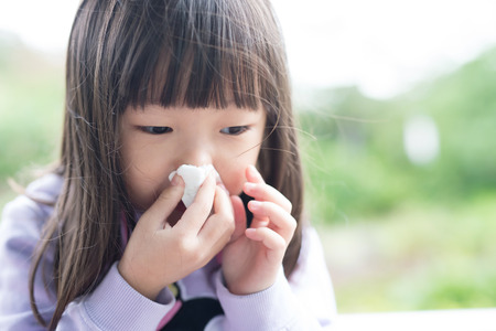 blowing nose: little girl get cold and blow her nose,  asian