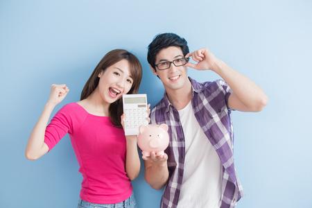 mantenga la pareja joven batería rosada del cerdo y calculadora aislados sobre fondo azul