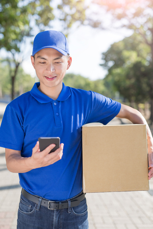 post: deliveryman hold box and talk on phone, asian