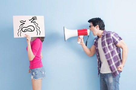 men and women: man take the microphone shout to woman angrily  isolated on blue background