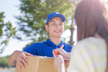 Deliveryman stehen und lächeln Kunden, asiatisch Standard-Bild - 72095867