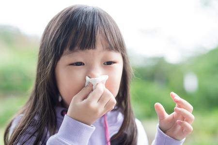 小さな女の子得る寒さと打撃彼女の鼻、アジア