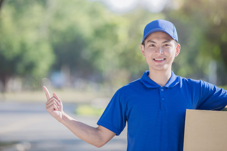 deliveryman hold  box and show something, asian