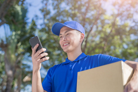 deliveryman hold box and talk on phone, asian